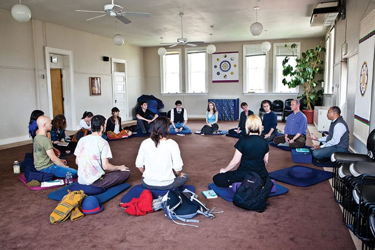 Gaylon Ferguson, at Naropa University, sits on the floor with students as he leads the graduate-level interdisciplinary course