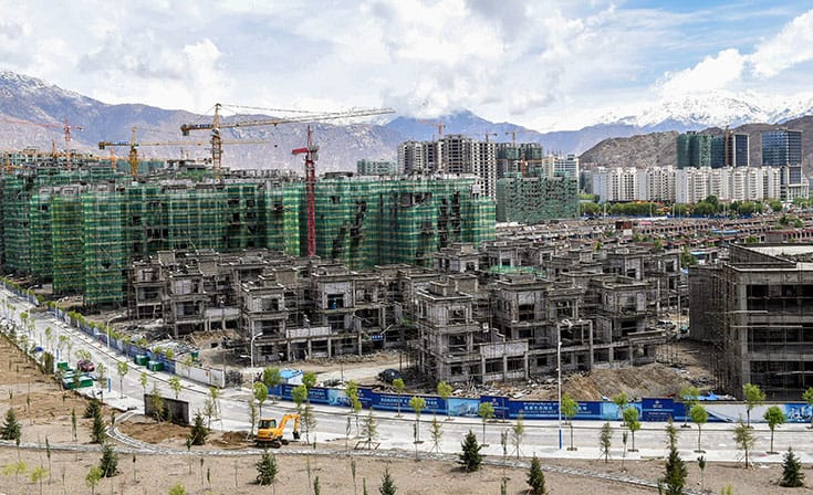 Apartment buildings sprout up in the suburbs of Lhasa. The rapid urbanization of Tibet is driven by Han Chinese immigrants and rural Tibetans seeking economic opportunity. Beijing has spent $100 billion to develop the Tibetan economy. Photo by Xinhua / Alamy Stock Photo.