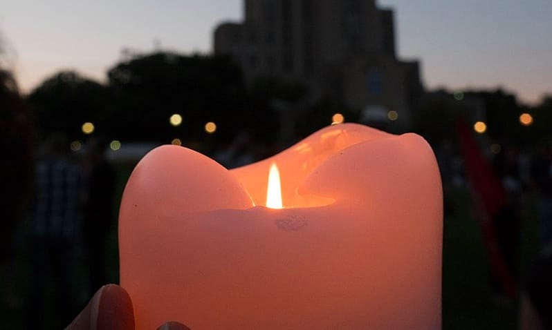 A pink lit candle being held up against a city background.
