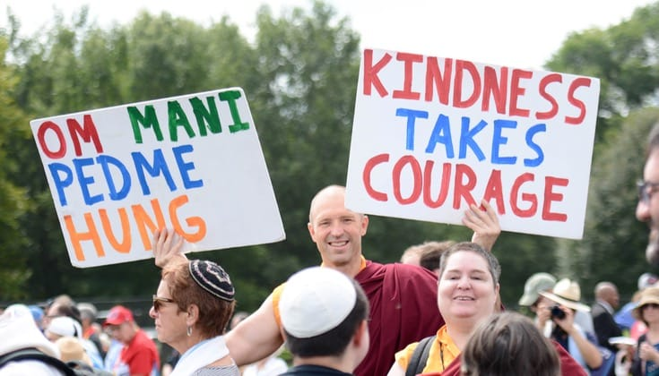 "A Buddhist monk stands in a crowd holding one sign that says ""Om Mani Padme Hung"" and another that says ""Kindness takes courage."""
