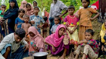 A Rohingya refugee family lives on the side of the road without shelter in Bangladesh.