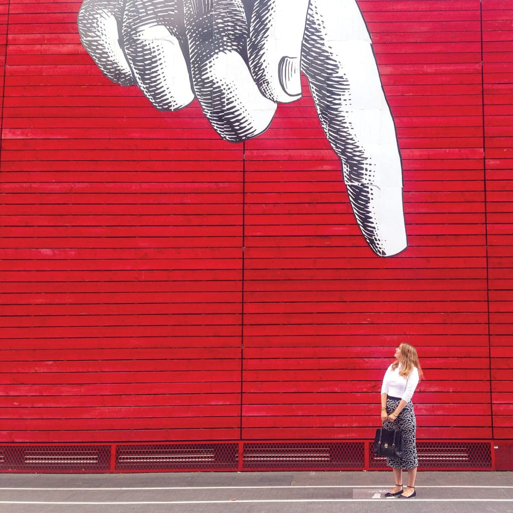 Street art of a finger pointing down at the ground. A woman stands under it.