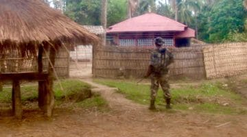 A soldier stands guard at the entrance to a house.