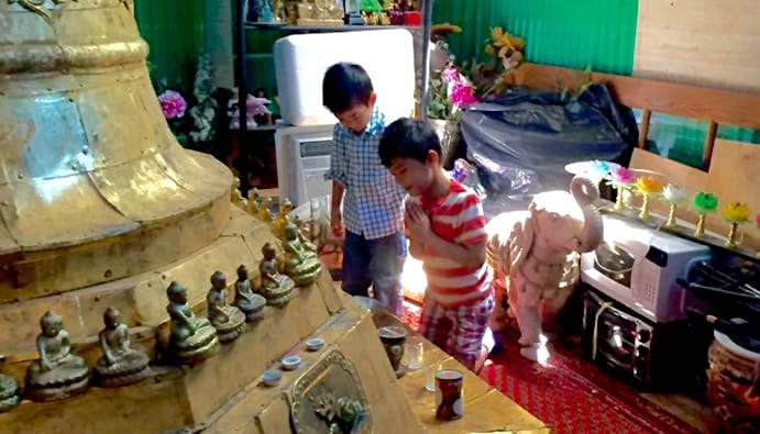 Two boys bowing to a stupa.