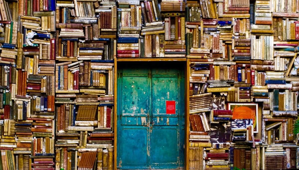 Wall of books with door.