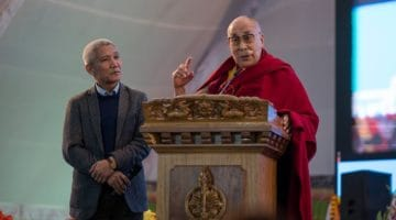 Dalai Lama speaking at lectern with Thupten Jinpa.