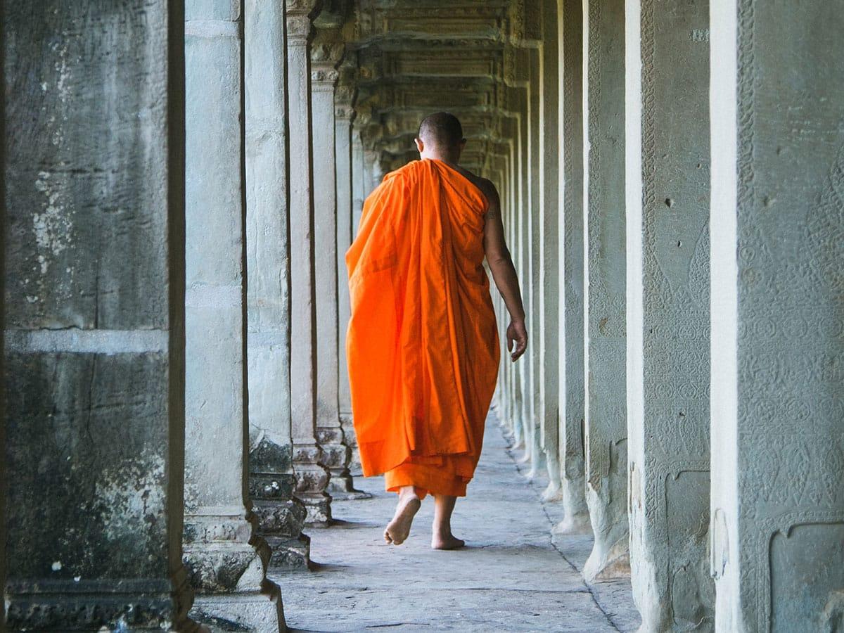 Person walking through pillars with orange monks robes.