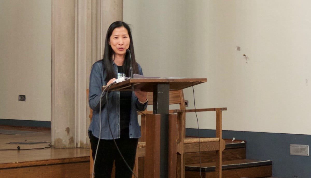 Rebecca Li speaking at a lectern.