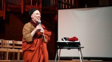 Bhikkhu Bodhi holding a microphone.