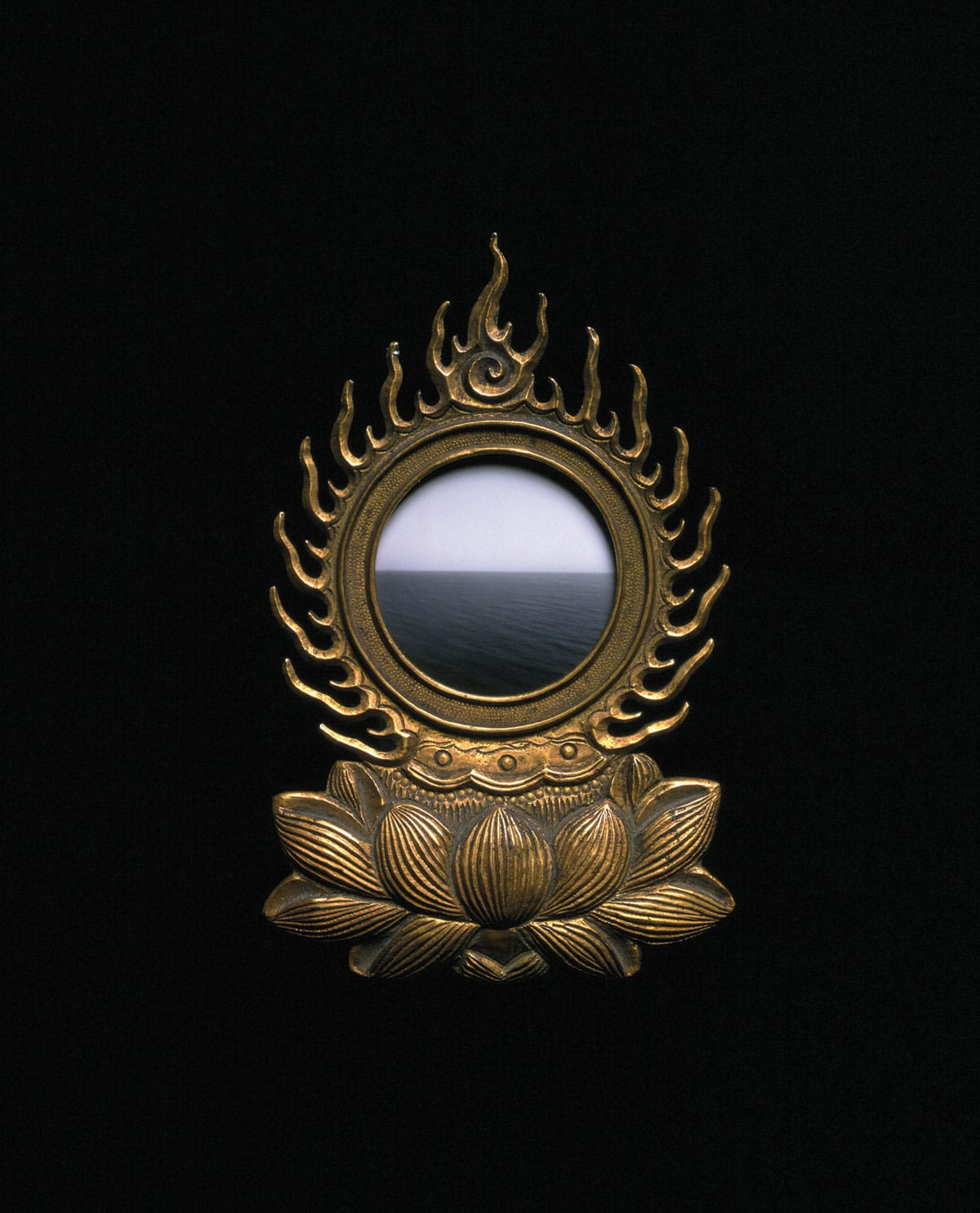 A brass mirror reflecting the ocean against a black wall.