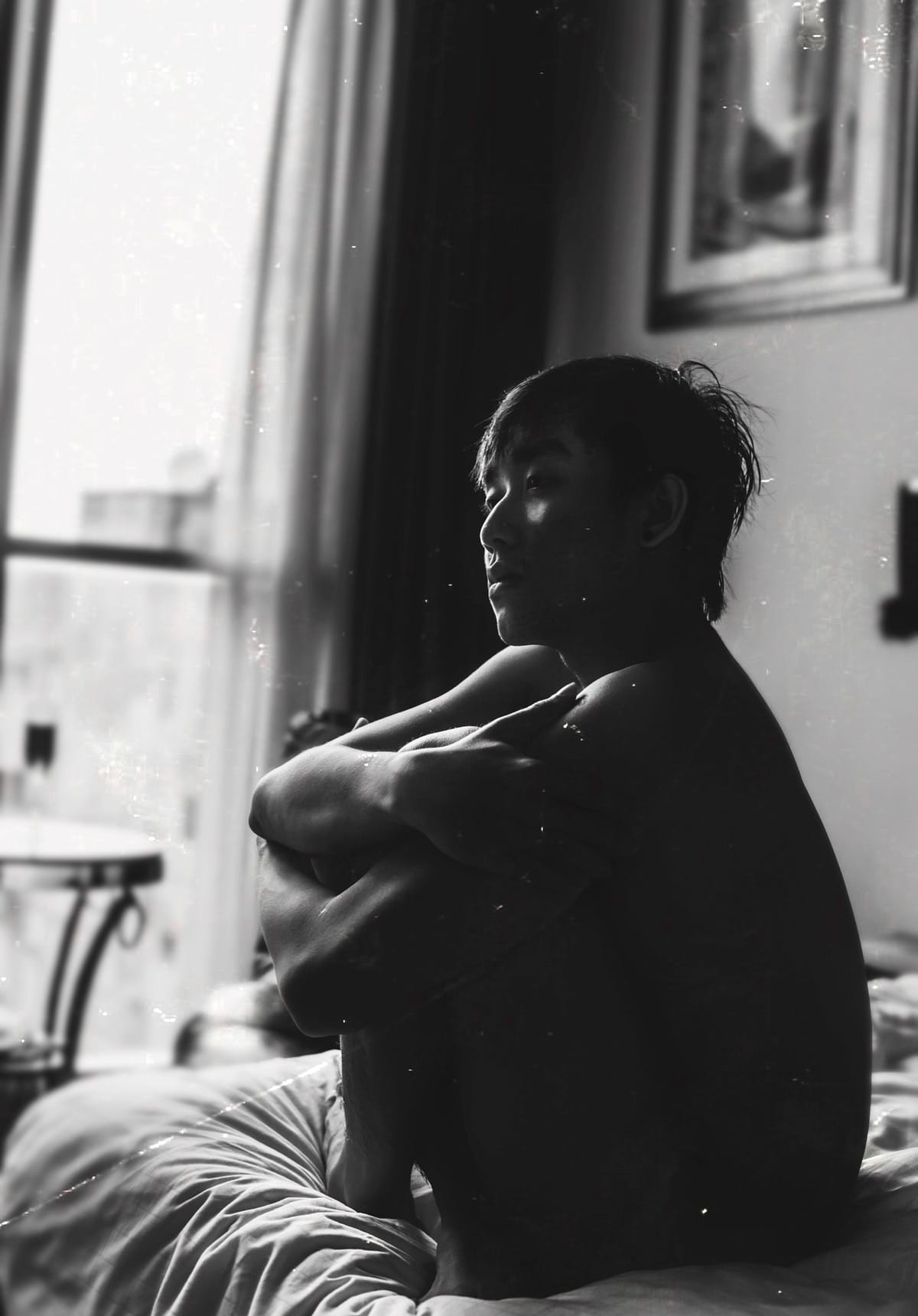 Man sitting cross-legged on bed.