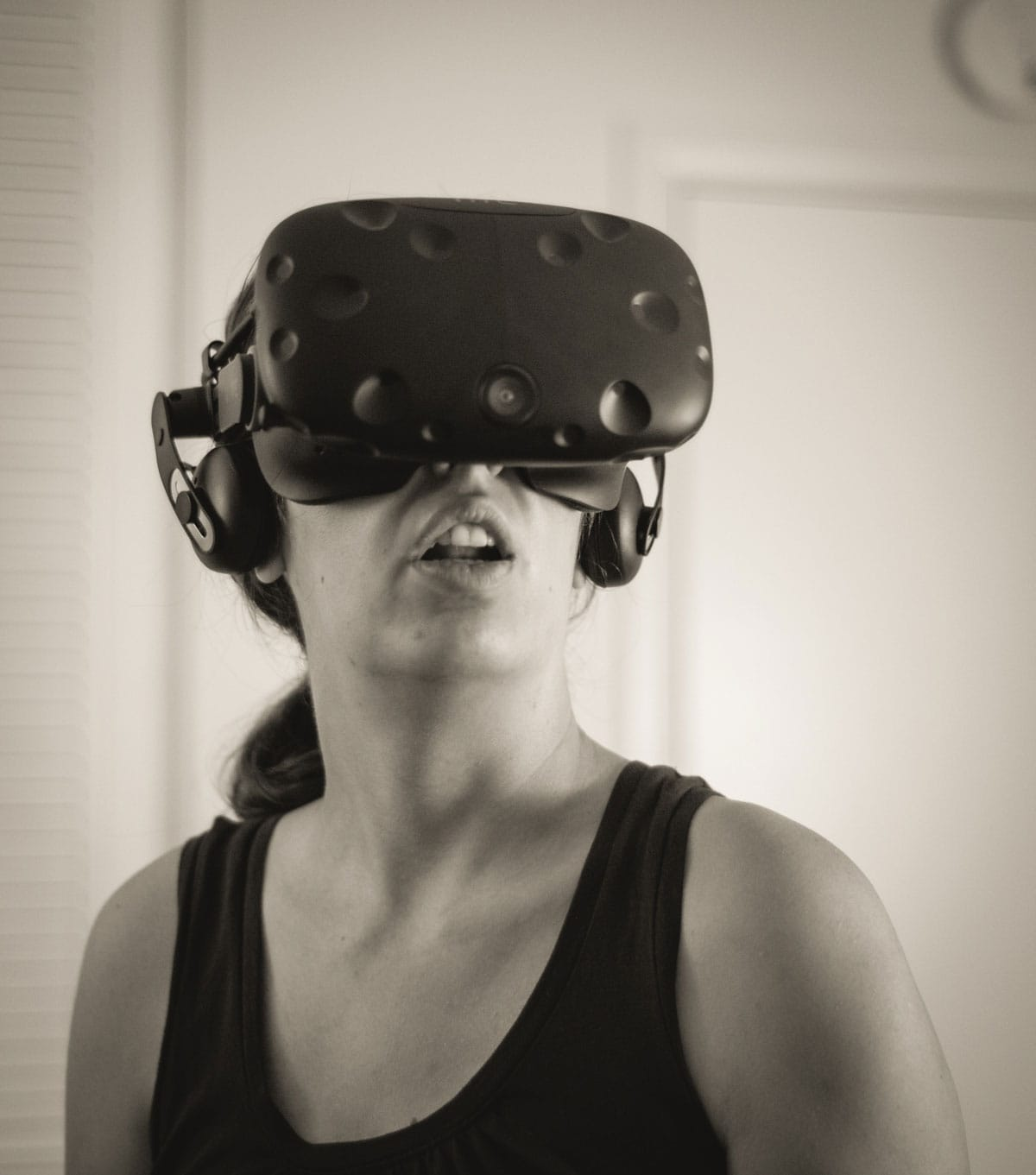 A black and white photograph of a person with virtual reality goggles.