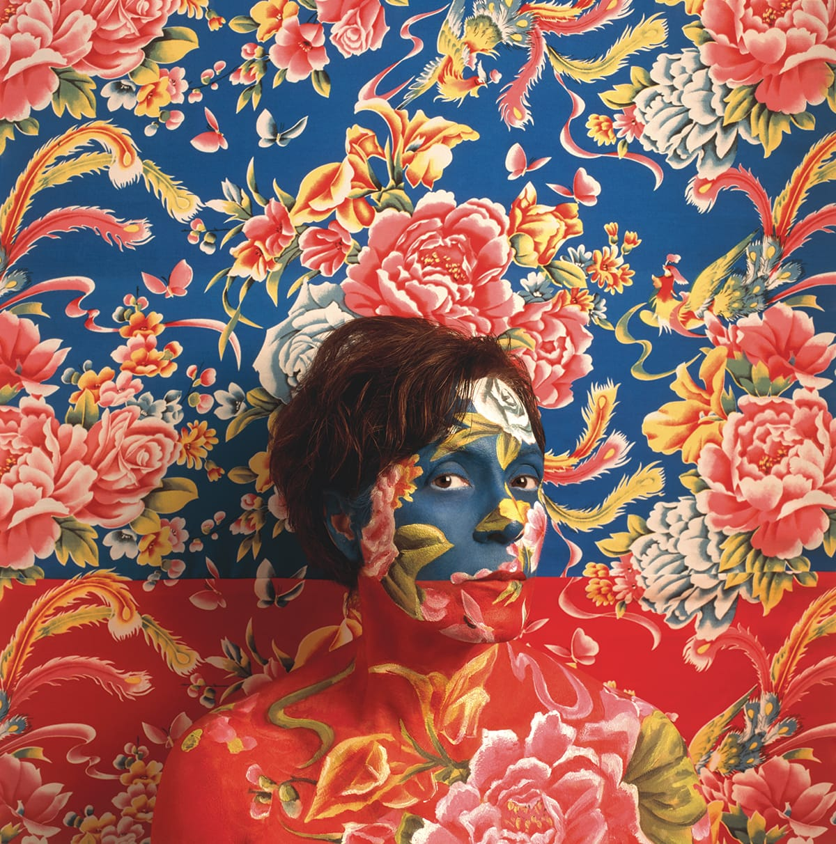 A woman standing in front of a floral wall. Her face is painted to match the floral pattern.