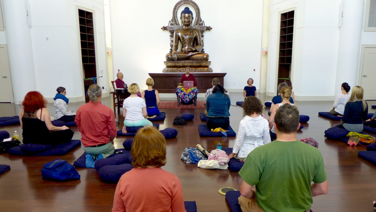 Main shrine hall with participants, teacher, and Buddha statue.