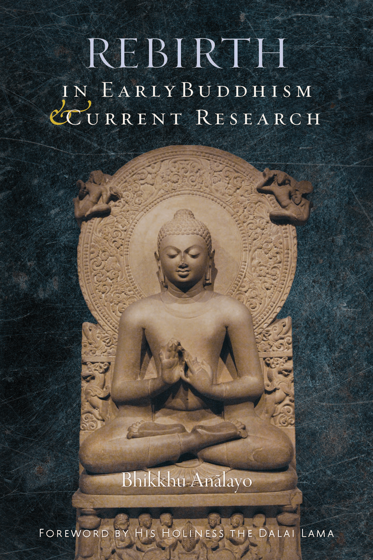 """Book cover for """"Rebirth in early buddhism and current research."""" It shows a statue praying against a blue wall."""
