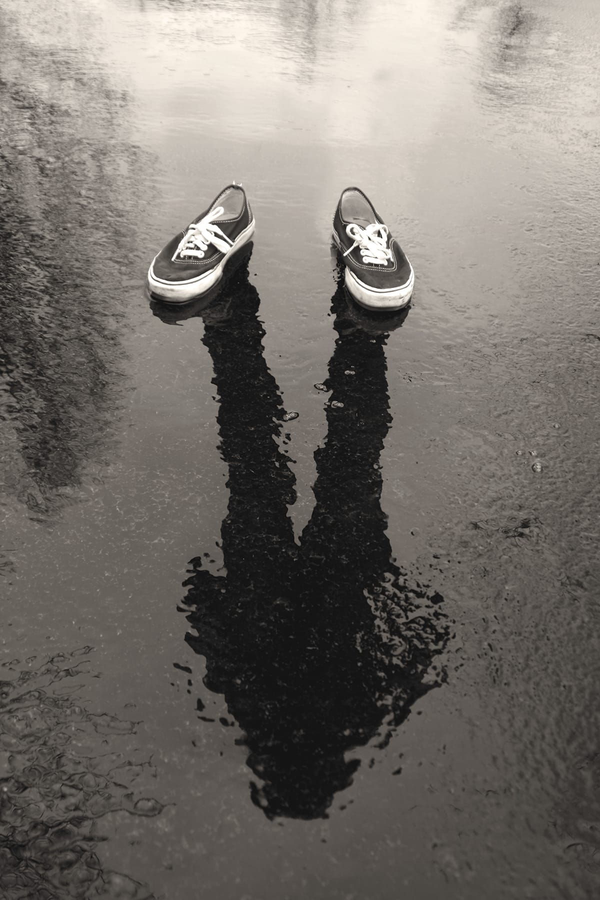 A black-and-white photo of a man's reflection on wet pavement with a pair of shoes on top of the reflection.