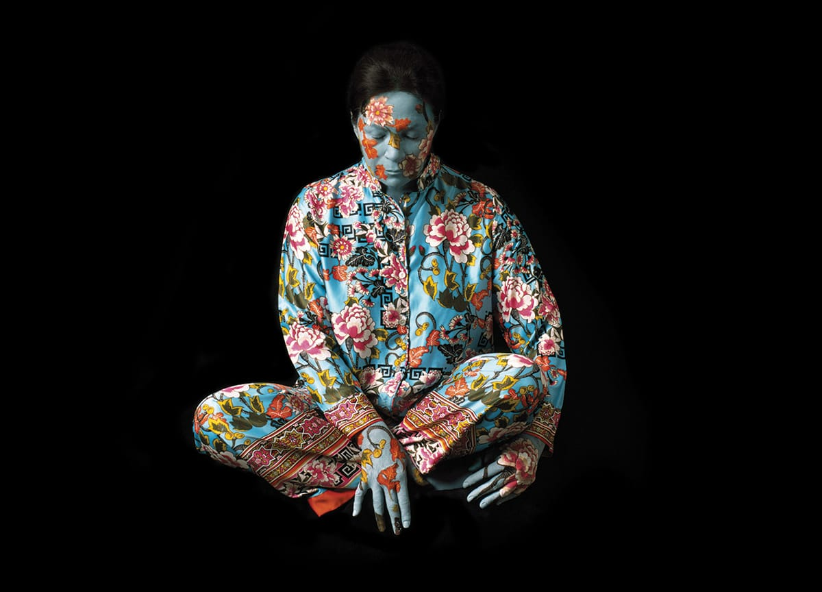 A woman wearing a floral printed silk outfit. Her face is painted like the pattern.