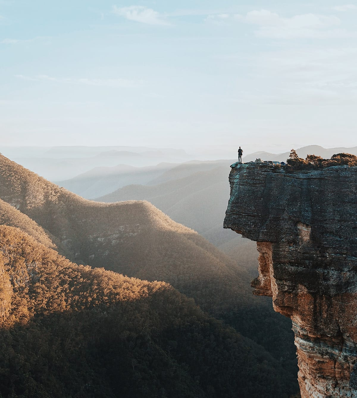 A person standing on the edge of a very large cliff.