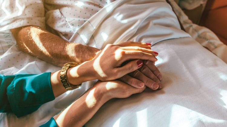 A woman holding a man's hand in a hospital bed.