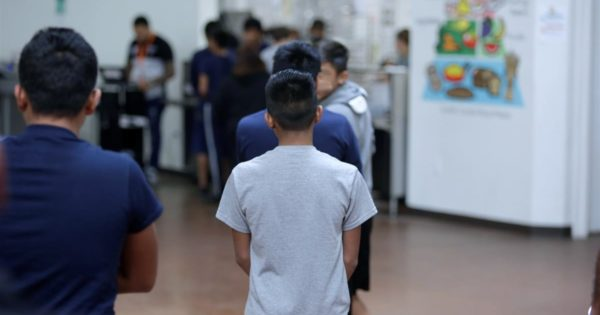 Boy stands in line in a detention center.