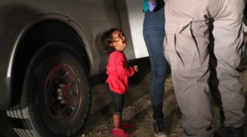 Small girl crying while border guards search her mother.