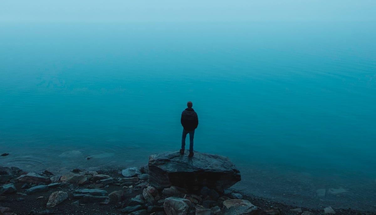 Man standing on rock in front of ocean.