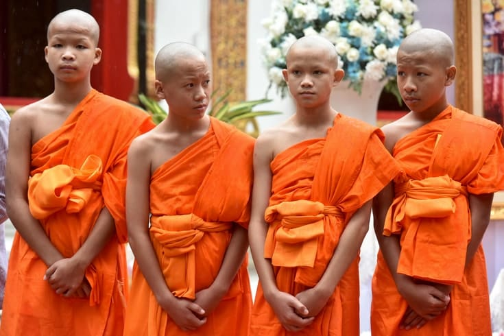 Four young monks standing in a row.