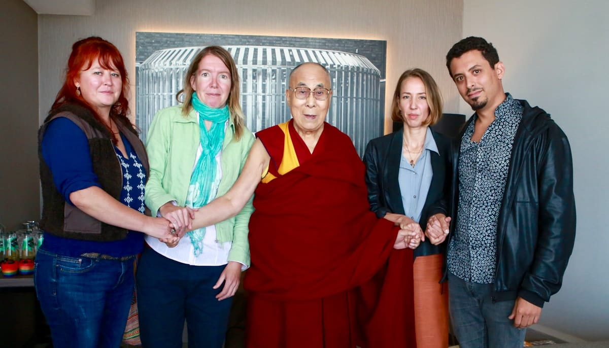 The Dalai Lama holding hands with four others.