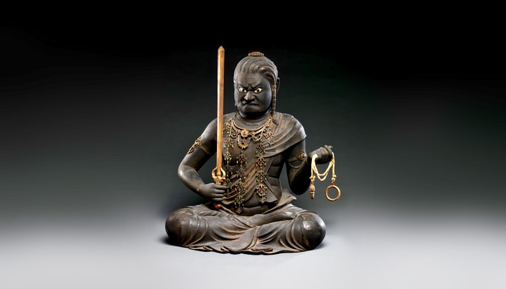 Sculpture of wrathful being Acala, holding a sword and a chain, sitting in meditation posture.