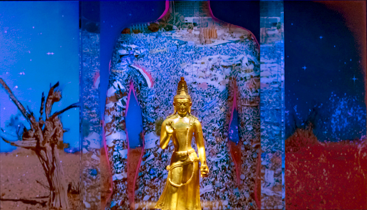 Statue of maitreya in front of a projected animation.