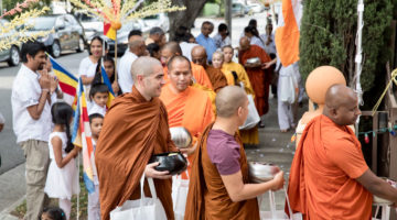 Monks in orange robes walking on alms rounds in Los Angeles.