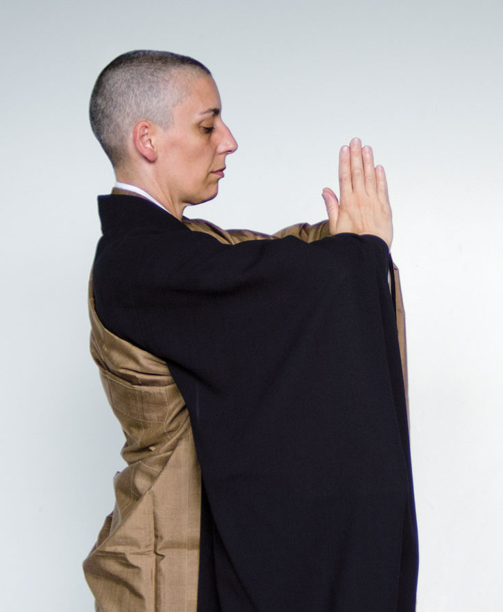 A person stands in monks robes with their hands pressed together in front of their chest.