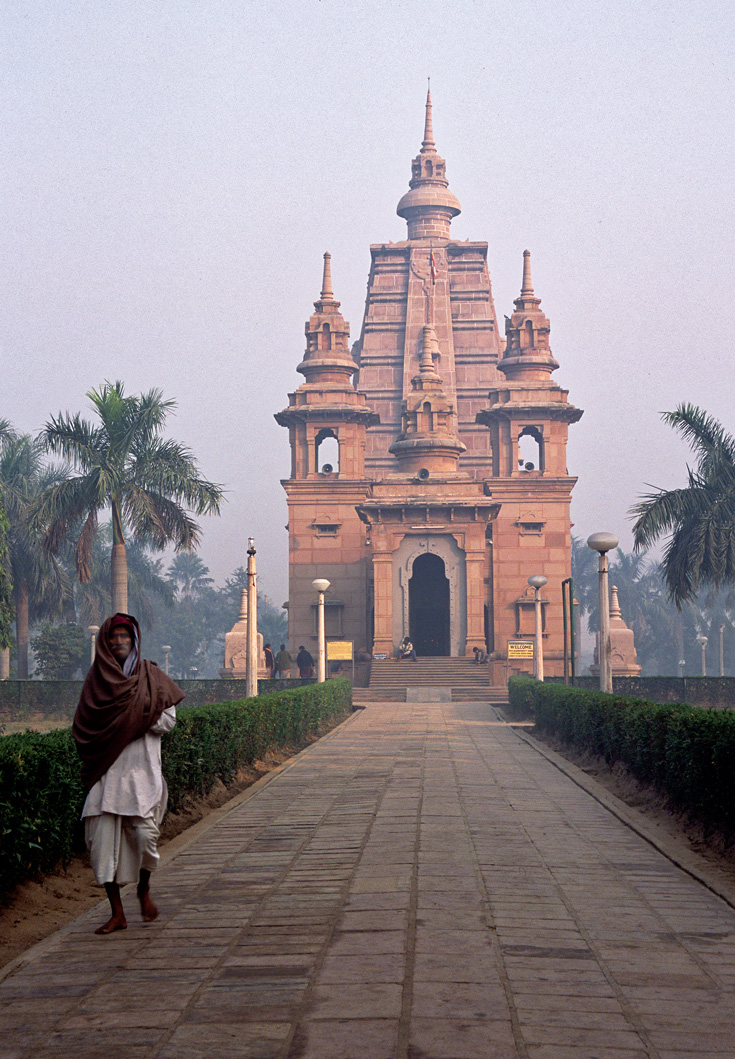 A person walks outside a path near a temple. It is a photo taken at sunset.