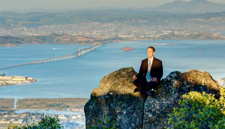 Man in a business suit sitting on a hilltop, meditating, with city skyline in background.