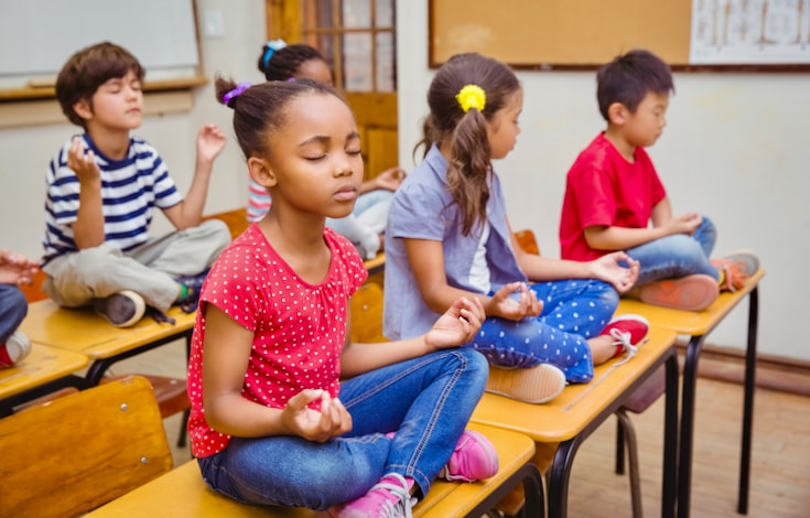 Children meditating on their desks.