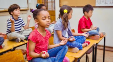 Children meditating on desks.