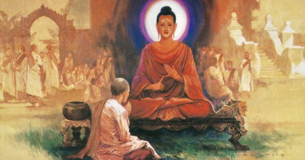 A woman with a shaved head bows before the Buddha.