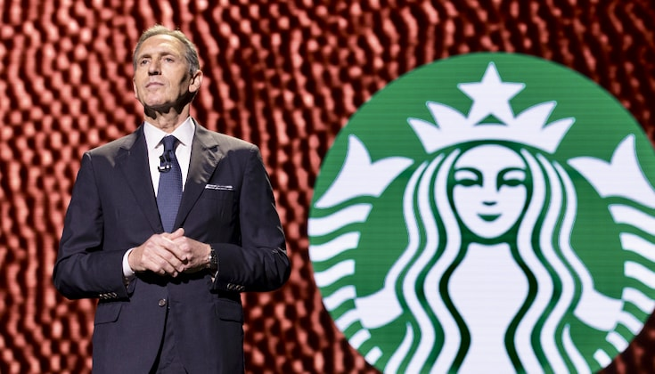 Howard Schultz stands on a stage in front of a Starbucks logo.