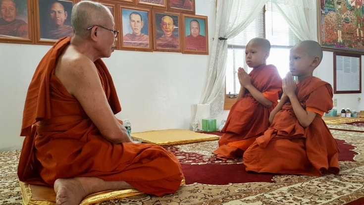 Two boy monks bowing to an elder monk.