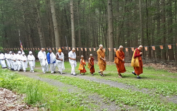 A group of people all walk in a straight line. The people in the left half are all wearing white, and the people on the right are all wearing orange.
