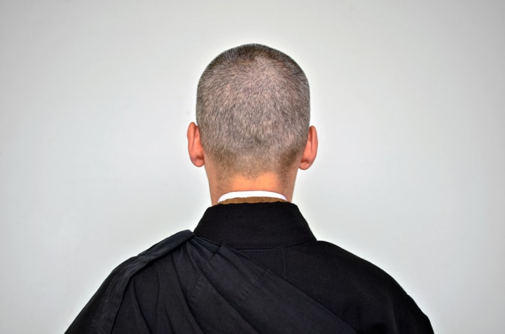 A photo of a monk taken from behind. Only the back of the head and the black robe is visible. Photo is taken against a grey wall.