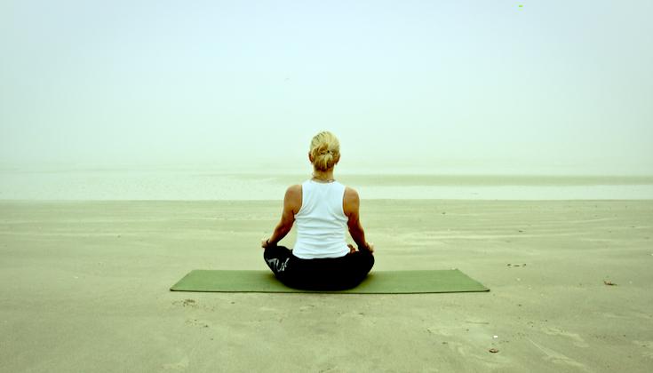 Woman meditating on a foggy beach.