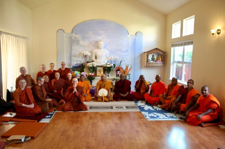 A group of monks and nuns sitting on the floor of a shrine room for an ordination ceremony.