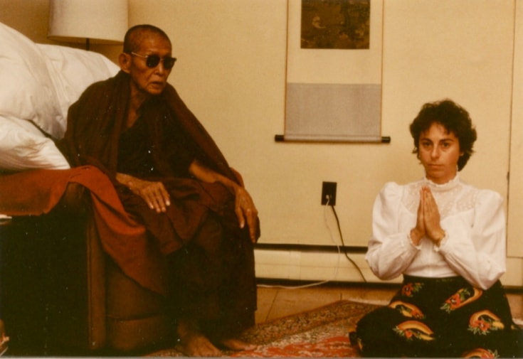 Jacquelline Mandell sits on the floor next to an elder monk, Taungpulu Sayadaw