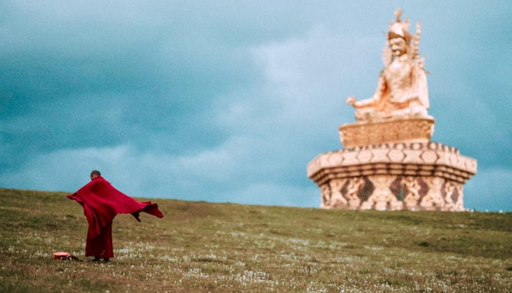 A monk standing in a field, with a statue of Padmasambhava in the distance.
