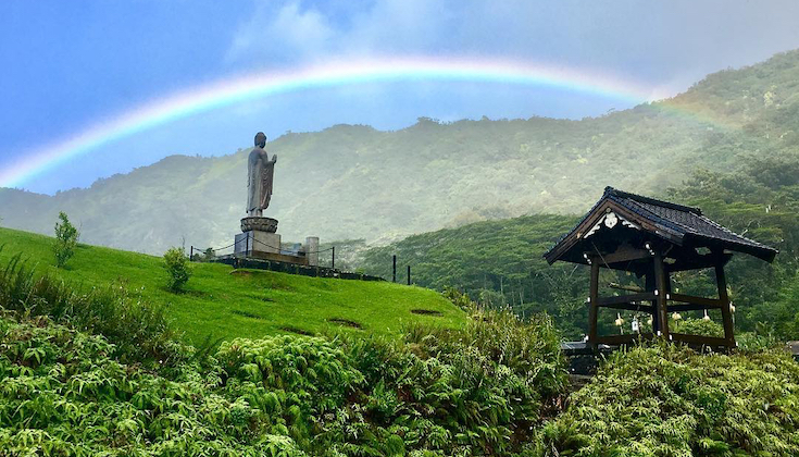 A rainbow over a Buddha statue.