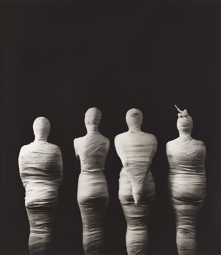 Photo taken from the back with four mummified people.