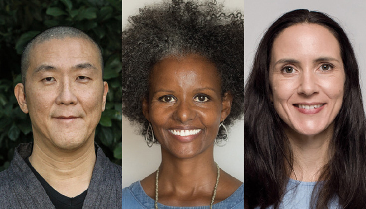 A photo of three people. The man on the left is bald and wearing a grey top. The woman in the middle has on hoop earrings and a necklace. The woman on the right has long hair and a blue shirt.