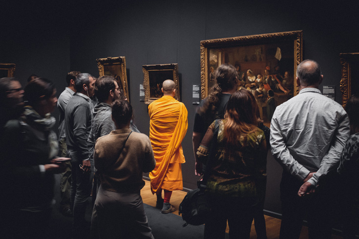 A photo of a bunch of people in an art museum. There is one man dressed in monk's robes.