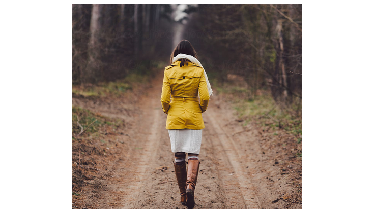 Woman in a yellow jacket walks down a muddy path.